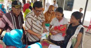 Teks foto: Ervida dan Ichsan dari PT Jiep memberikan sumbangan makanan tambahan balita di Posyandu Mekar Indah RW 10 Petukangan Pulojahe Jaktim.. Foto: ist.